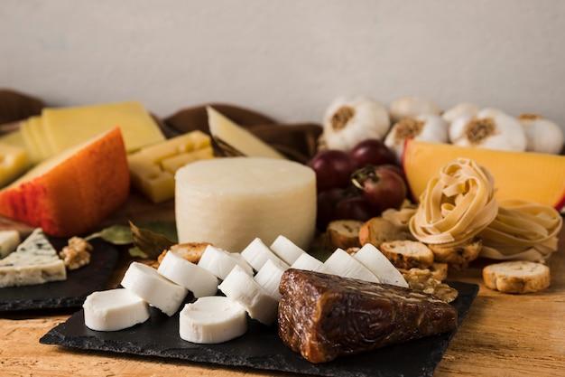 さまざまな種類のチーズとテーブルの上の食材 無料写真