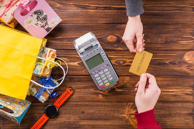 木製のテーブルにスワイプマシンとゴールドのカードを保持している人間の手の立面図 無料写真