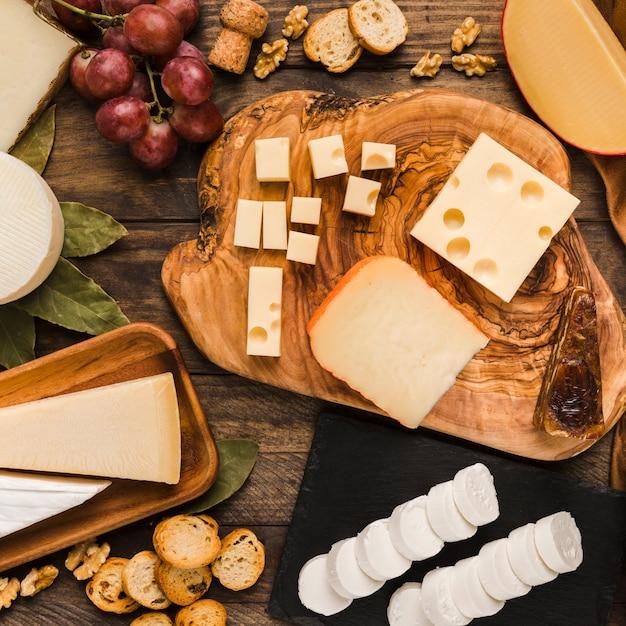 木製の机の上のおいしい成分とチーズボード上のナチュラルチーズの部分 無料写真