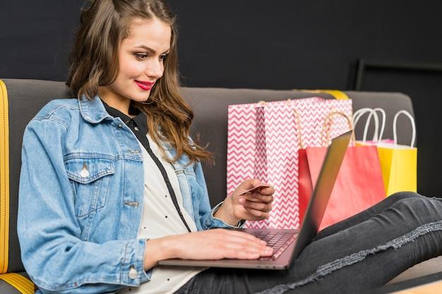 オンラインショッピングを楽しんで家で座っている幸せな女 無料写真