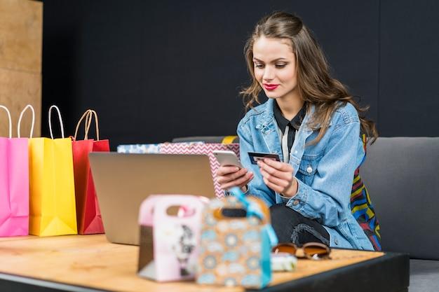 女性が自宅でのオンラインショッピングのための携帯電話とスマートカードを使用して 無料写真
