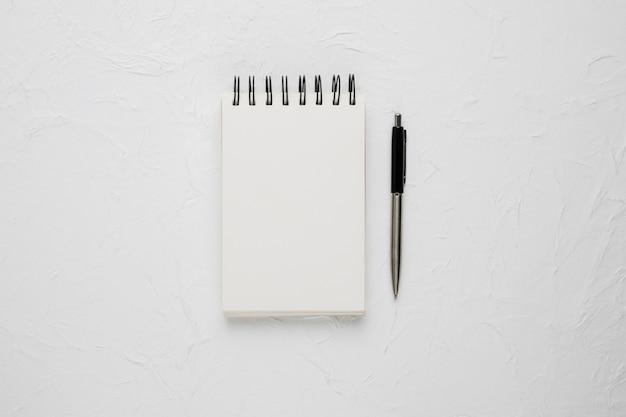ボールペンと白い空白のスパイラルメモ帳の高角度のビュー 無料写真