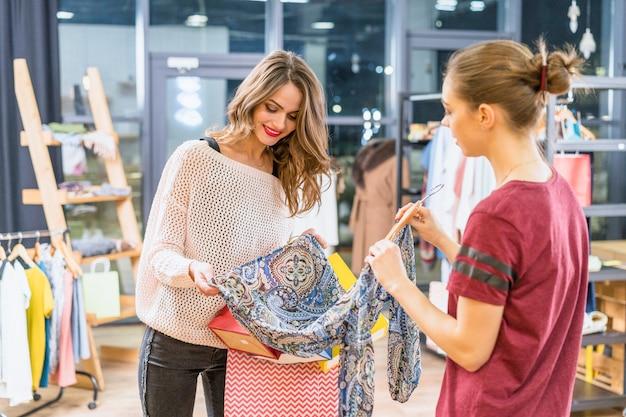 Консультант показывает одежду женскому покупателю в торговом центре Бесплатные Фотографии