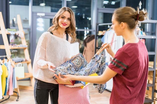 Привлекательная молодая женщина, покупая одежду в магазине одежды Бесплатные Фотографии