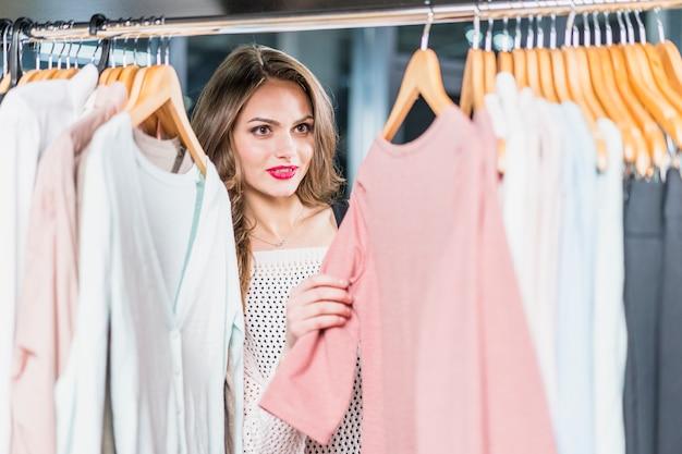ショールームのラックに服を選ぶ若い女性 無料写真