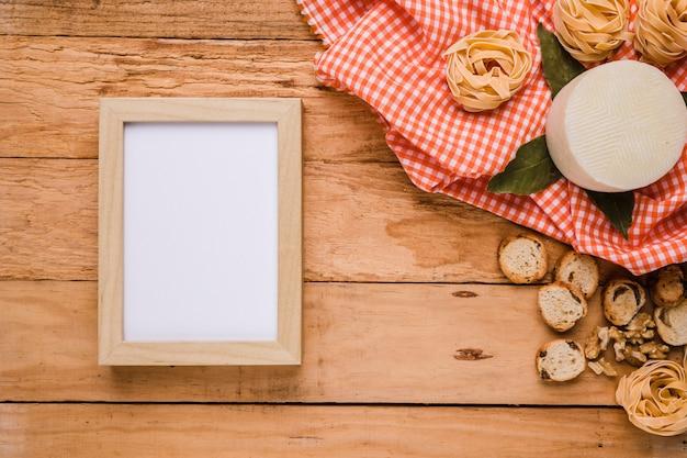 木製のカウンターの上の市松模様のテーブルクロスとおいしい食べ物の近くの空の図枠 無料写真