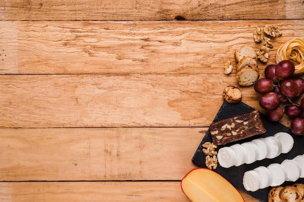 スレートの石の上にチーズと健康的な原料の立面図 無料写真