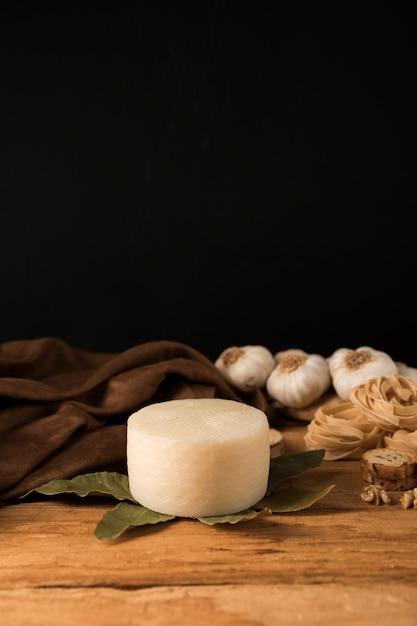 スペイン産マンチェゴチーズ、月桂樹の葉、生パスタ、木製のテーブルの上のニンニクの球根 無料写真