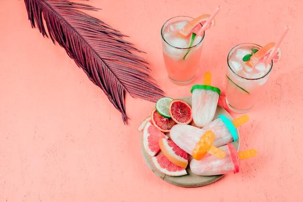 グレープフルーツスライスジュースとアイスキャンディーのテクスチャ背景の上の葉を持つアイスキャンデー 無料写真