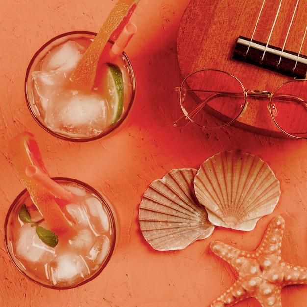 貝殻ウクレレ;眼鏡と織り目加工の背景にストローでジュースのグラス 無料写真