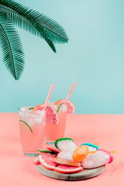 グレープフルーツのカクテルグラスの上に手のひらが落ちます。ティールの背景に対してサンゴの机の上のアイスキャンディー 無料写真