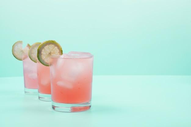 レモンスライスとミントの背景にアイスキューブと赤いカクテルグラス 無料写真