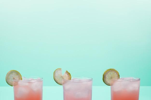 レモンスライスとミントの背景に対してアイスキューブとカクテルのグラス 無料写真