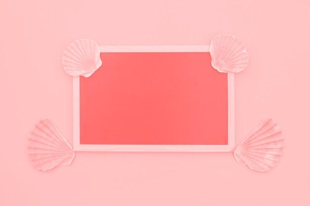 ピンクの背景にホタテ貝殻で飾られた空白のサンゴフレーム 無料写真