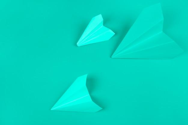 ミントの背景にグリーンペーパー飛行機の俯瞰 無料写真