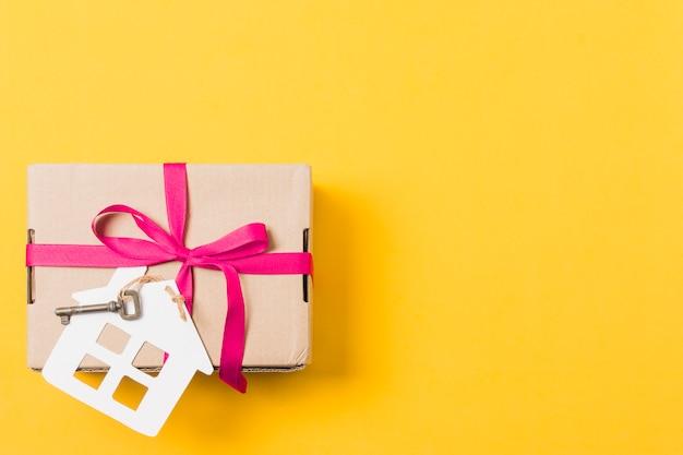 ギフト用の箱は明るい黄色の背景上のキーと家のモデルと結ばれる 無料写真