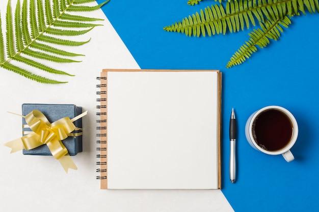 プレゼントボックススパイラルメモ帳。ペンと紅茶シダの葉のデュアル背景 無料写真