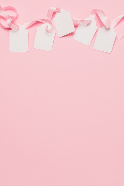 白いタグと背景の上にテキスト用のスペースとピンクのリボン 無料写真