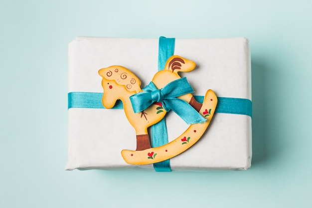 Крупный план подарочной коробки и качалки игрушка связана с голубой лентой на фоне Бесплатные Фотографии