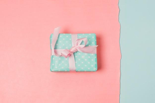 青と桃の背景の上のプレゼントボックス 無料写真
