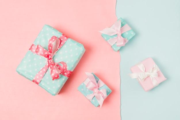 Маленькие и большие декорированные подарочные коробки перевязаны ленточкой на персиковых и синих обоях Бесплатные Фотографии