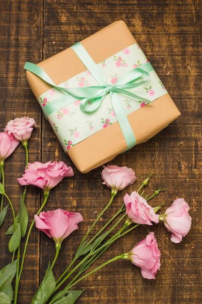 Крупный план обернутой посылки и розовый свежий цветок на столе Бесплатные Фотографии