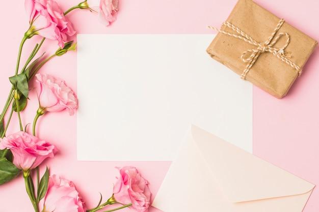 白紙の封筒付き。新鮮なピンクの花とピンクの背景の上の茶色の包まれたギフトボックス 無料写真