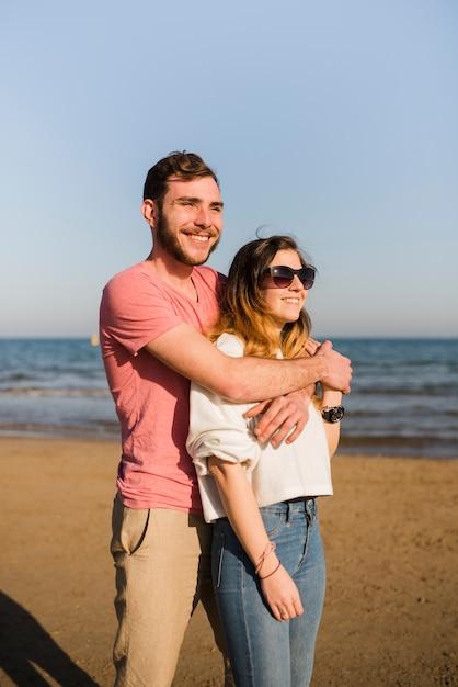 ビーチを離れて見ている海岸近くに立っている幸せなカップルの肖像画 無料写真