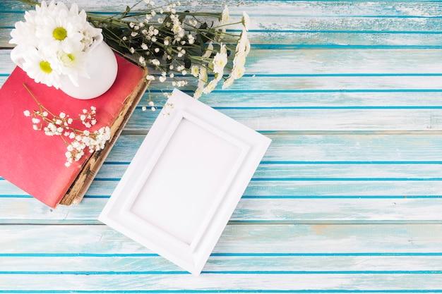 テーブルの上の空白のフレームとデイジーの花 無料写真