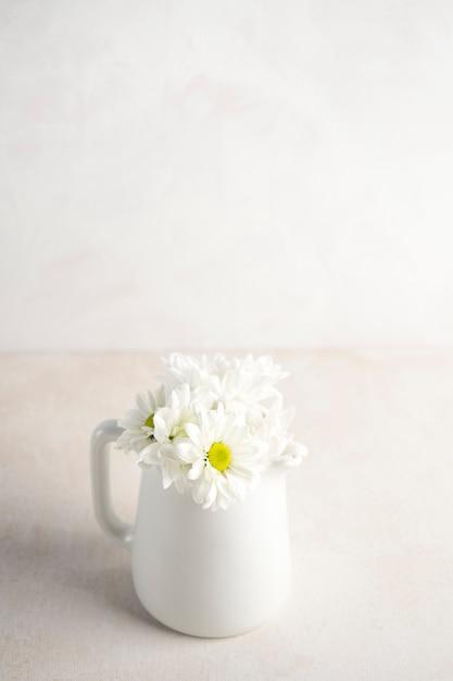 テーブルの上の水差しのデイジーの花 無料写真