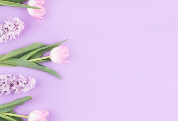 紫色のテーブルの上に花とピンクのチューリップ 無料写真