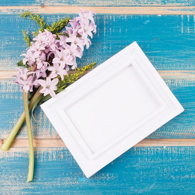 テーブルの上の花を持つ空白のフレーム 無料写真