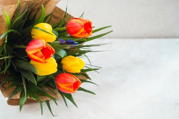 テーブルの上のパック紙のチューリップの花の花束 無料写真