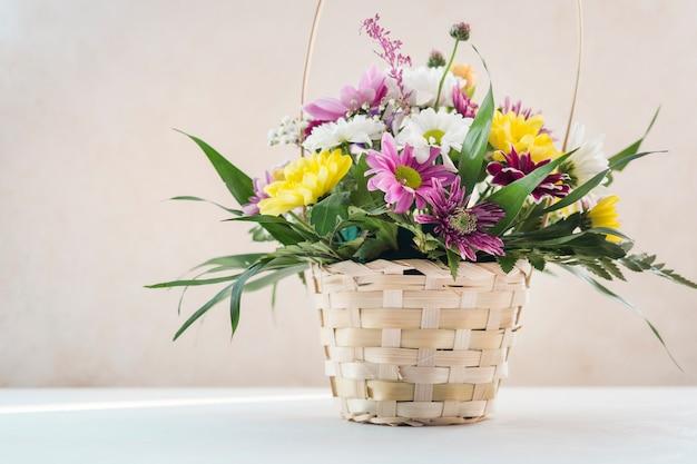 テーブルの上の枝編み細工品バスケットの花の組成 無料写真