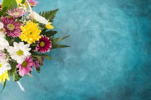 青いトーンの机の上に置かれた明るい花束 無料写真