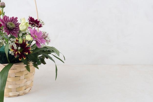 灰色の背景上の花と枝編み細工品バスケット 無料写真