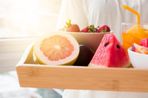 Женщина, держащая различные фрукты ломтиками грейпфрута; арбуз и клубника в миске с соком стекла на деревянный поднос Бесплатные Фотографии