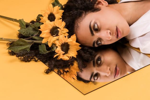 鏡で見ている花を持つ魅力的な民族のロマンチックな女性 無料写真