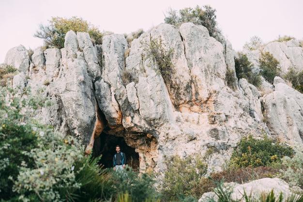 洞窟の前でハイカー 無料写真