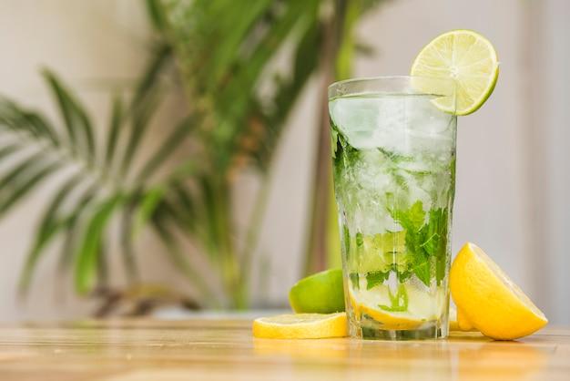 氷とボード上のハーブと飲み物のガラスの近くの果物のスライス 無料写真