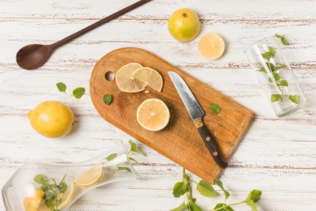 ハーブとグラスの間のナイフの近くの果物のスライス 無料写真