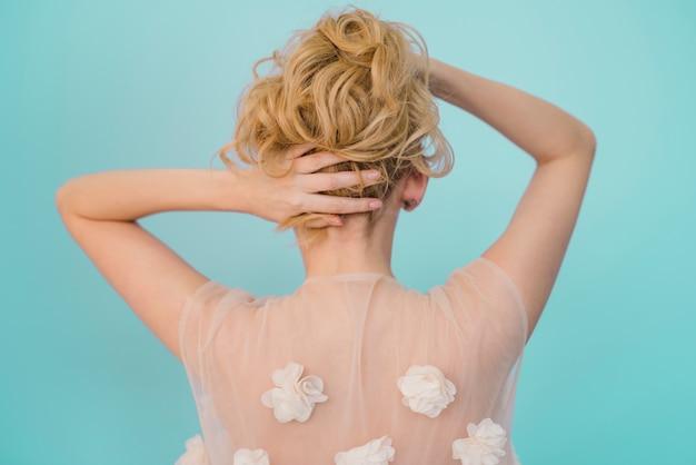 彼女の髪の世話をしているブロンドの女の子 無料写真