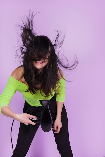 ヘアドライヤーでポーズブルネットの少女 無料写真