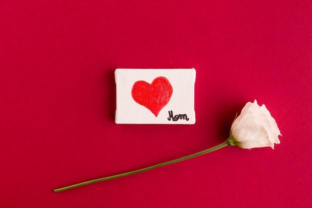 Название мамы и сердце на бумаге возле цветка Бесплатные Фотографии