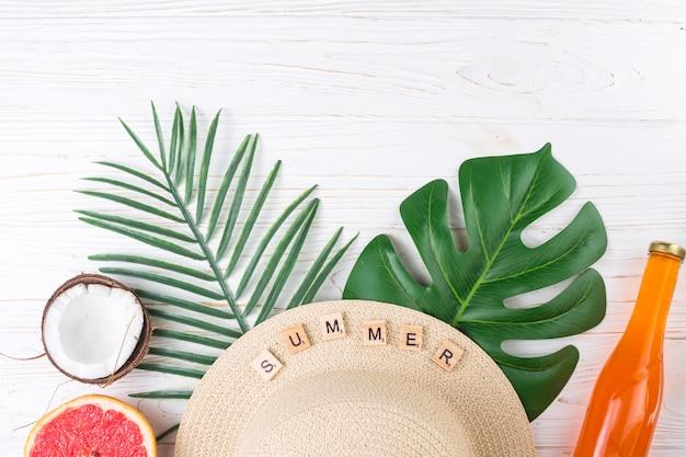フルーツとビーチ帽子のエキゾチックな休暇の手配 無料写真