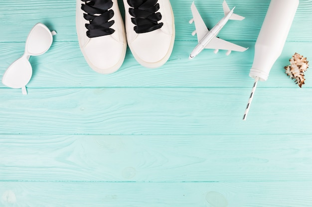 Белые расписные туфли с игрушечным самолетом и бутылкой с соломой Бесплатные Фотографии