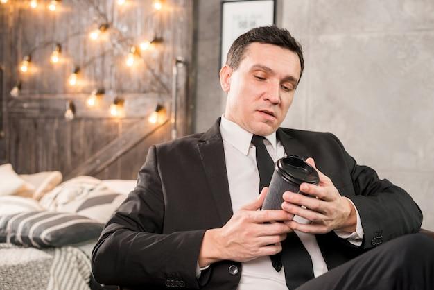 Мужчина рассматривает бумажный стакан кофе Бесплатные Фотографии