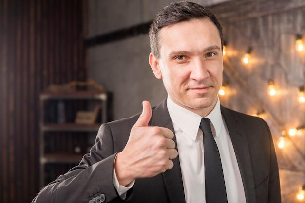 親指を現してスーツを着た男性 無料写真