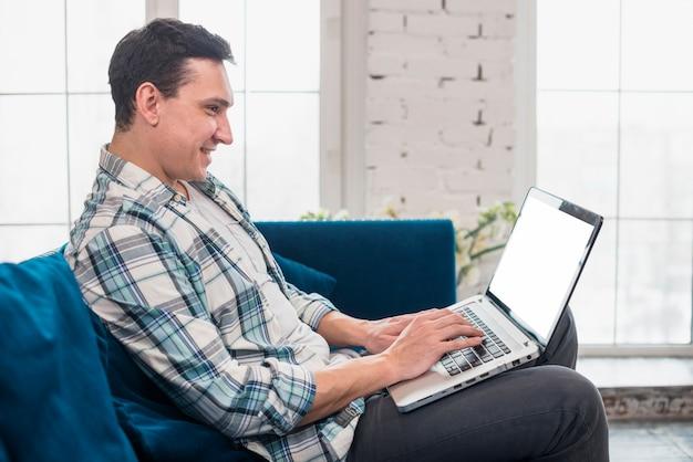 幸せな男が座っているとラップトップを使用して 無料写真