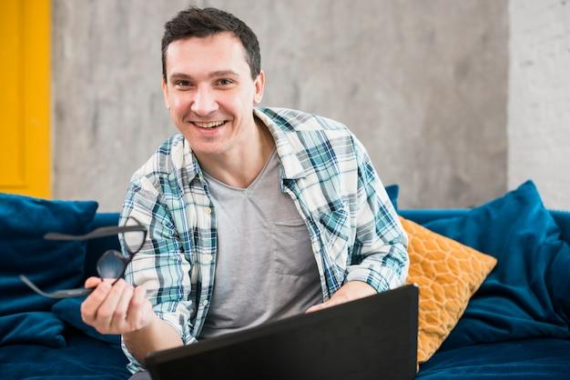 幸せな男性の居間でラップトップに取り組んで 無料写真